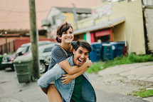 a happy couple, piggy back ride, man, woman outdoors