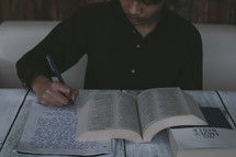 A young man taking notes as he studies the Bible.