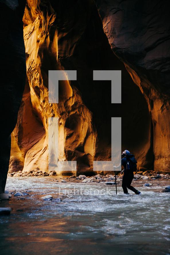 a man hiking through a river