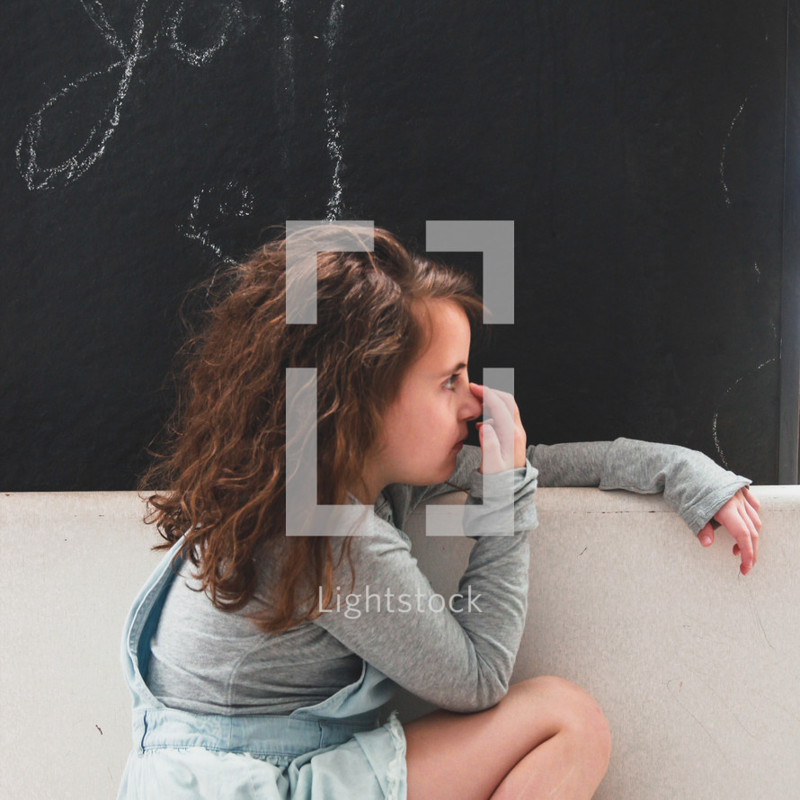 girl in front of a wall painted with chalkboard paint