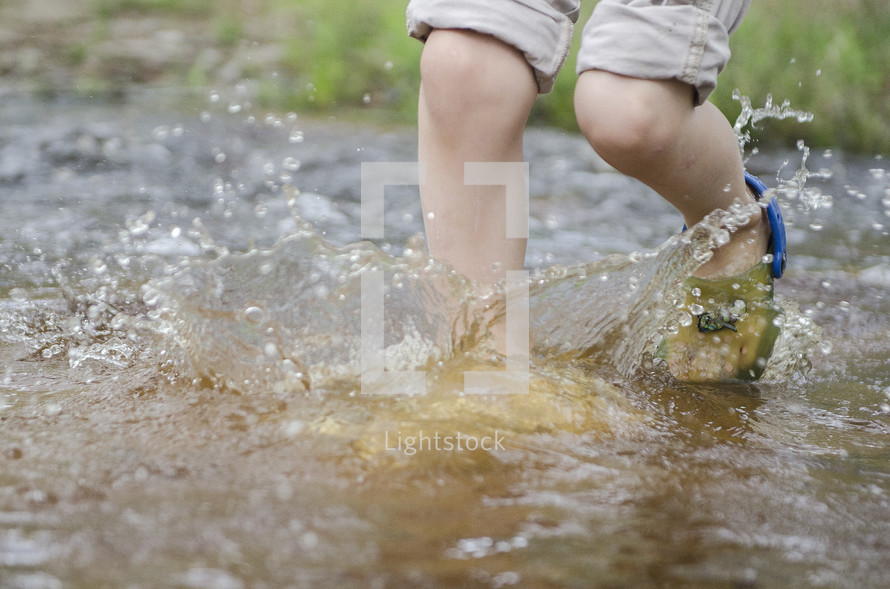 a toddler splashing in a puddle