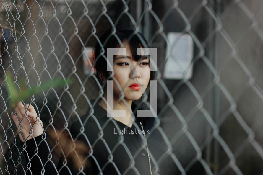 woman's face through a chain linked fence
