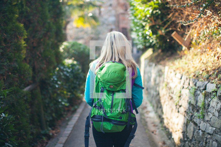 woman backpacking on a paved path