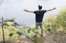 Teenager standing high on cliff overlooking lake with arms outstretched