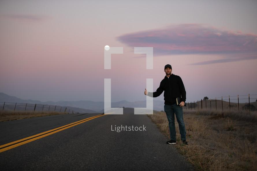 man holding a Bible hitchhiking