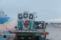 God is love sign and painted rocks
