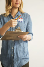 """A young woman with a clipboard and pencil and an """"I Voted"""" button."""