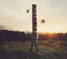 Person in a field balancing a very tall stack of books.