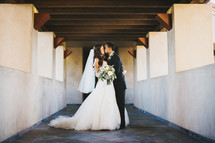 bride and groom kissing on a rooftop