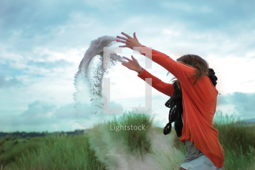 woman tossing sand in the air