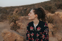 a smiling woman in a floral jacket