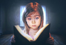 A little girl reading with a surprised expression