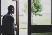 man holding open the doors of a church