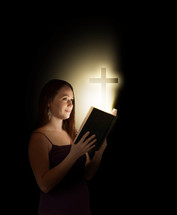 woman holding a glowing Bible with a cross