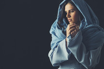 Mary in a blue shroud with praying hands