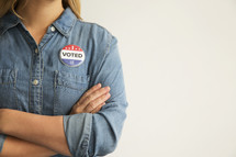 "A woman with arms crossed wearing a ""I Voted,"" button."
