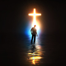 A man standing before a glowing cross.