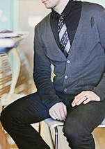 man in a sweater and tie sitting