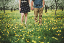 a couple holding hands in a field of wildflowers
