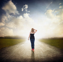 woman walking down a long open road