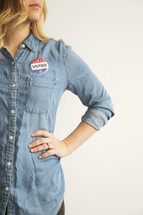 """A woman wearing a denim shirt and an """"I Voted,"""" button."""