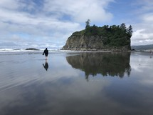 a person walking on wet sand on a beach