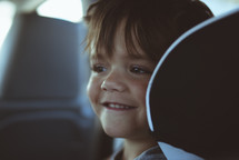 smiling child in the backseat of a car