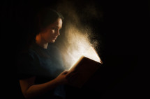 Woman reading an illuminated Bible.