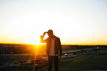 man touching his hat standing outdoors at sunset
