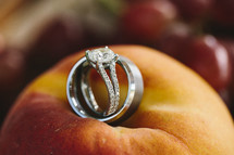 wedding band and engagement ring lying on a peach