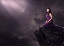 light shining on a woman on a rock in a purple dress