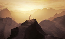 A woman standing at the top of a mountain with raised hands
