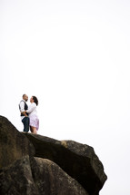 couple couple standing on top of a rock