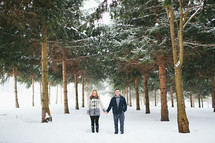 a couple holding hands in snow