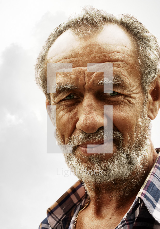 The face of a stoic elderly man