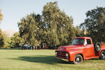 people gathered under a tree and an old vintage red truck