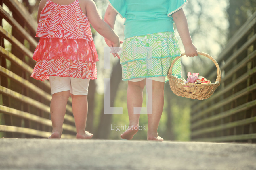 sisters walking bare foot holding hands with a basket