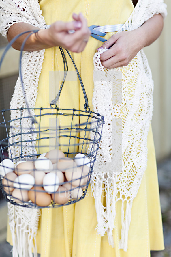 A woman with a wire basket of eggs.
