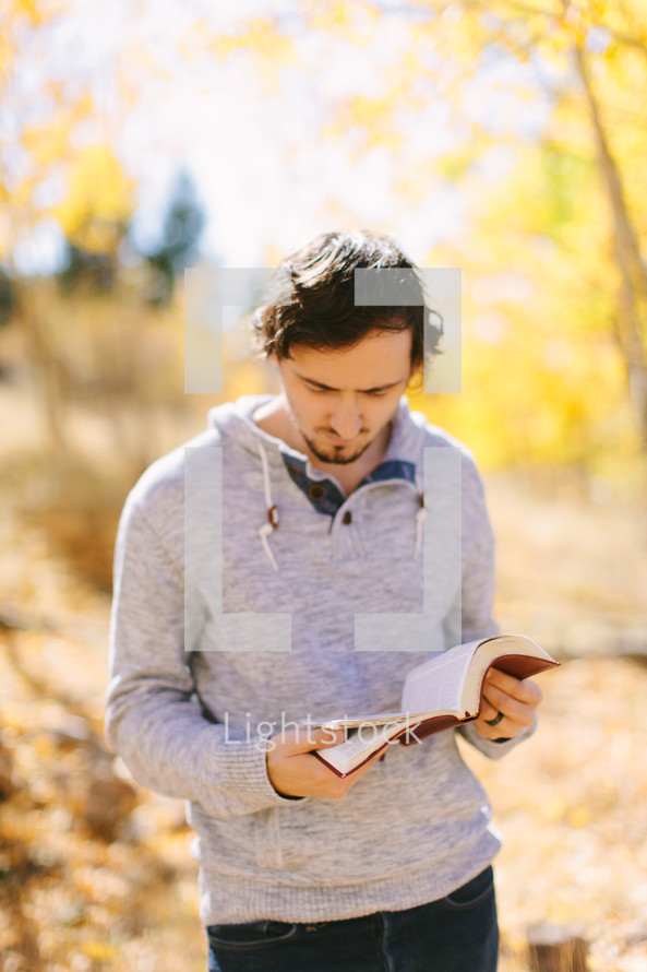 Standing outside during fall reading Bible