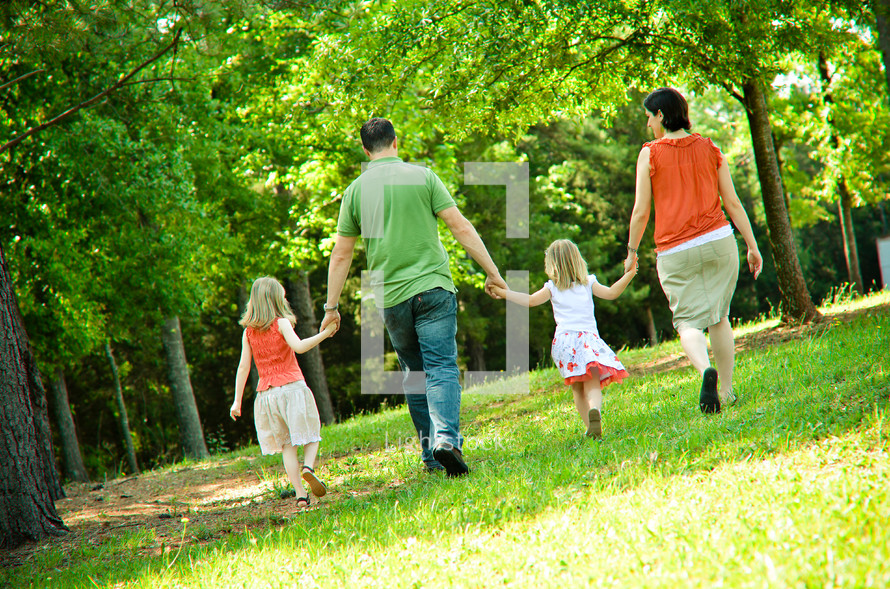 family walking in a park holding hands