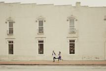 Couple running down sidewalk street
