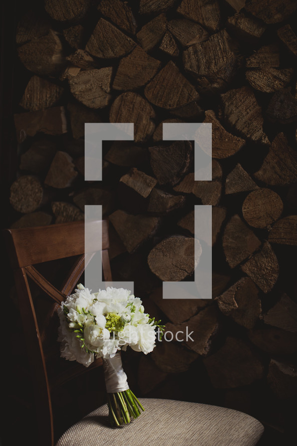 bouquet in a chair in front of a wood pile