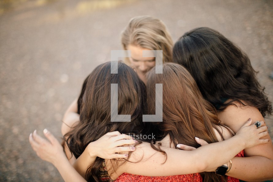 women holding hand in a prayer circle