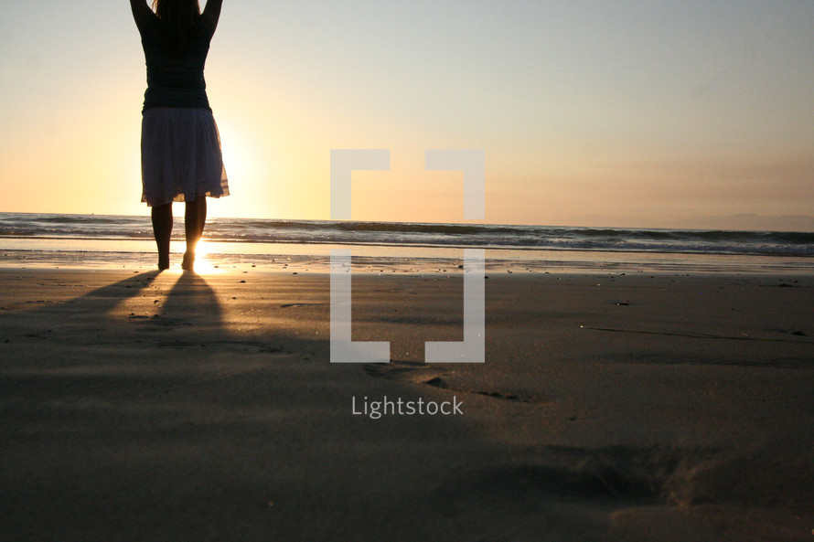 Woman standing on beach sand with raised hands