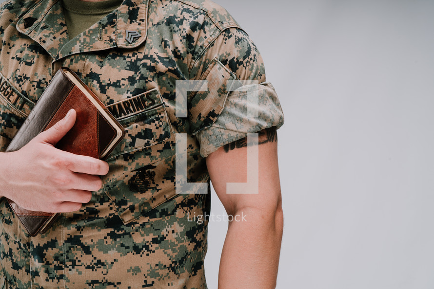 a marine holding a Bible to his chest