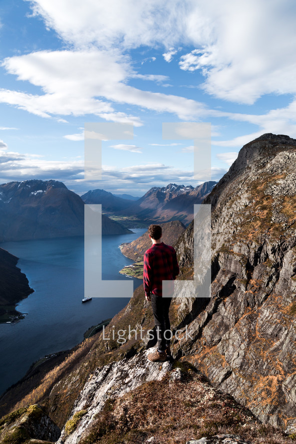 a man standing at the edge of a mountain looking out at the view