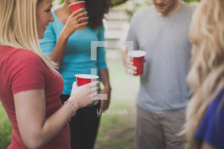 friends in conversation holding red cups at a party