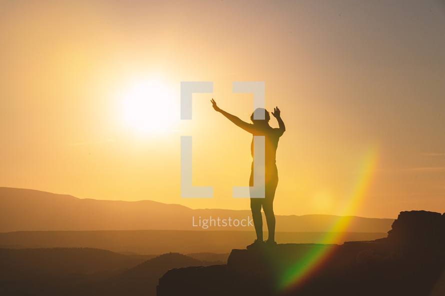a woman with raised hands standing at the edge of a mountain at sunset