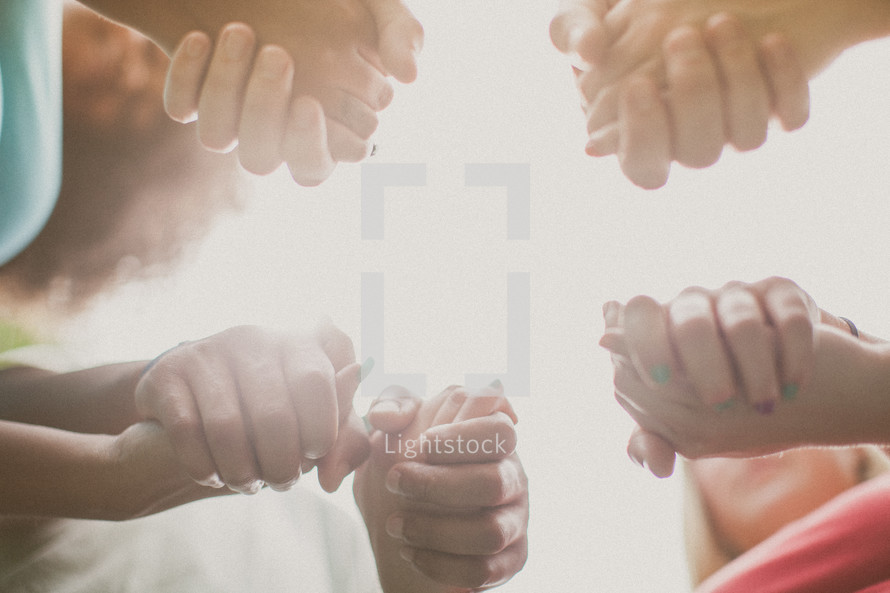 holding hands in a prayer circle