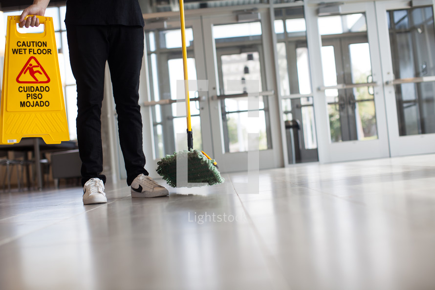 a man with a dust mop and wet floor sign in a lobby